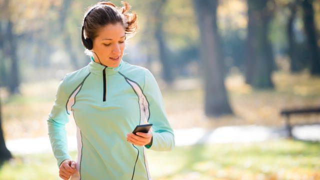 Frau hört mit Smartphone Apple Music beim Joggen