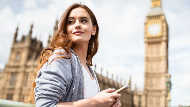 Junge Frau am Big Ben mit dem Smartphone