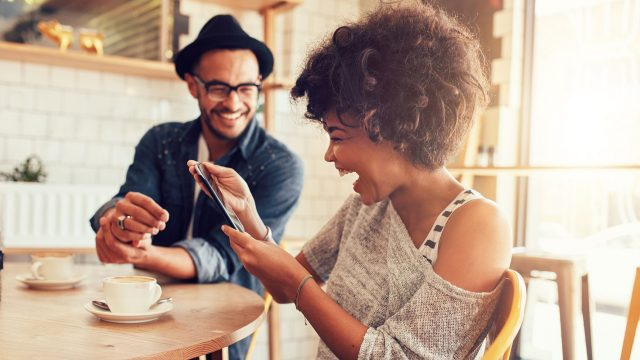 Lachende Frau mit Smartphone im Cafe
