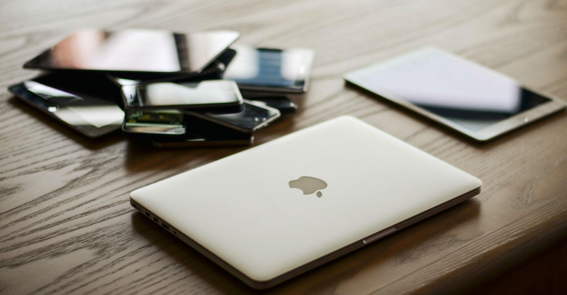 Ein Stapel an Smartphones, Tablets und einem Macbook von Apple.