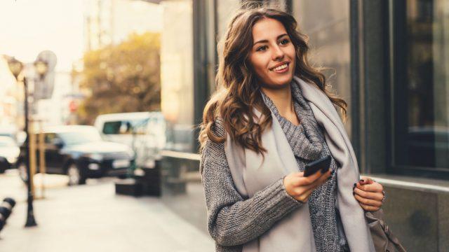 Junge Frau spaziert mit dem Smartphone.