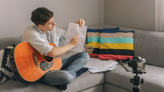 Junger Mann mit Gitarre filmt sich selbst