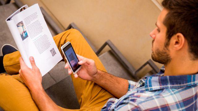 Ein Mann scannt einen QR-Code aus einer Zeitung ab.