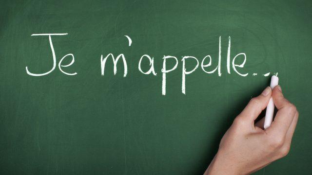 """Menschliche Hand malt mit Kreide den Satz """"Je m'appelle"""" an die grüne Tafel."""