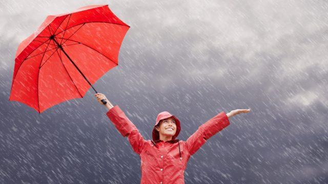 Frau mit Regenschirm lacht über den Regen