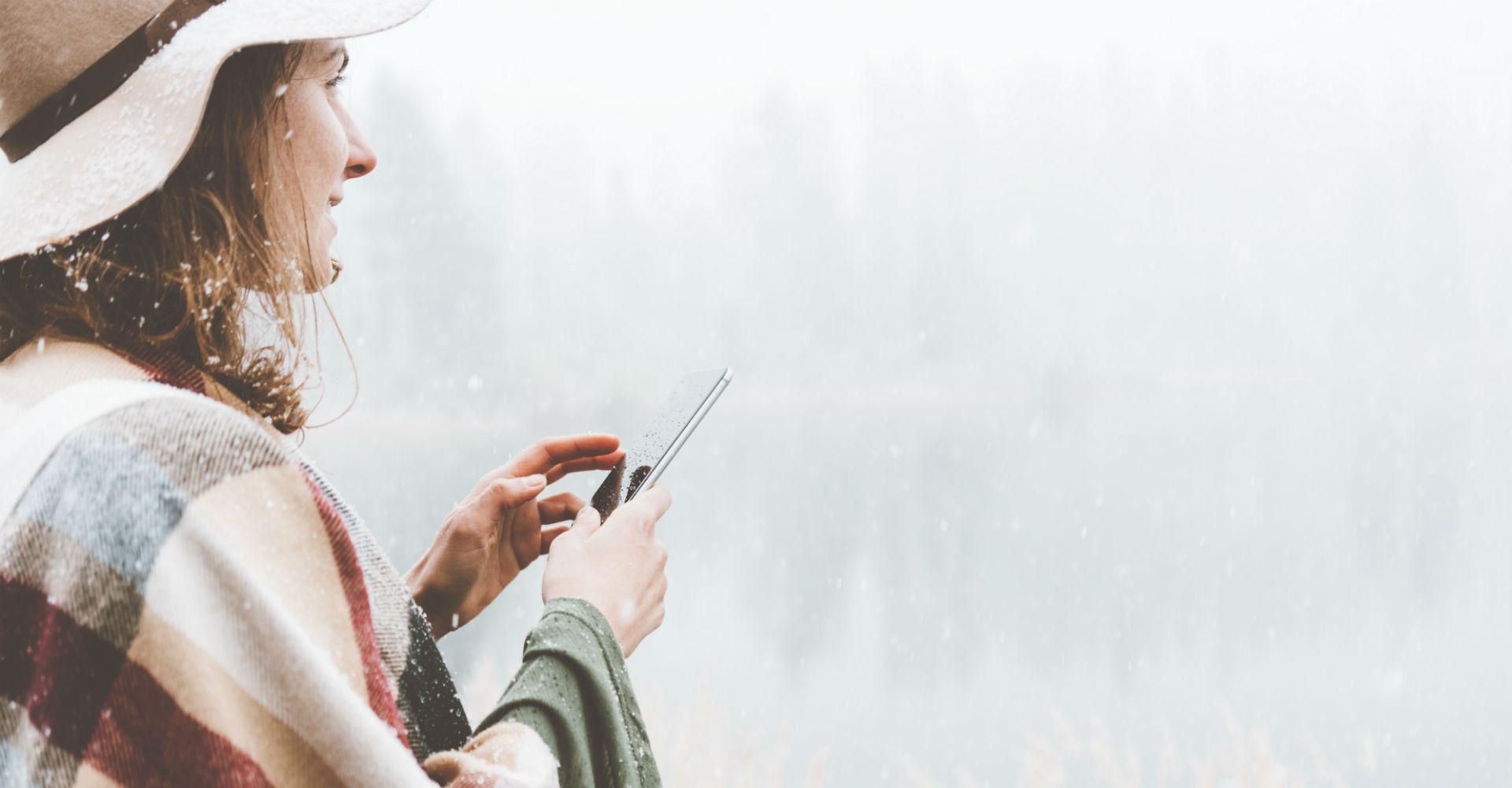 Junge Frau steht lächelnd im Schnee und hält dabei ein Smartphone in der Hand.