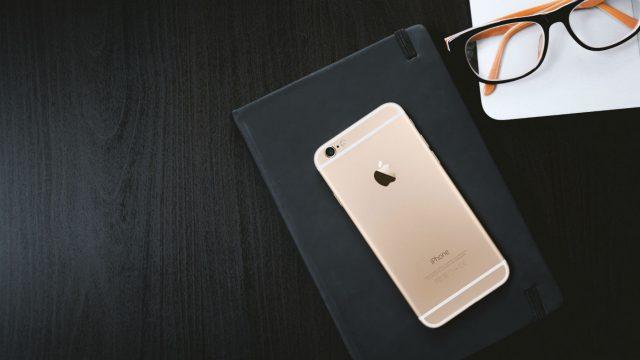 iPhone 6 liegt neben einer Brille auf einem schwarzen Tisch.