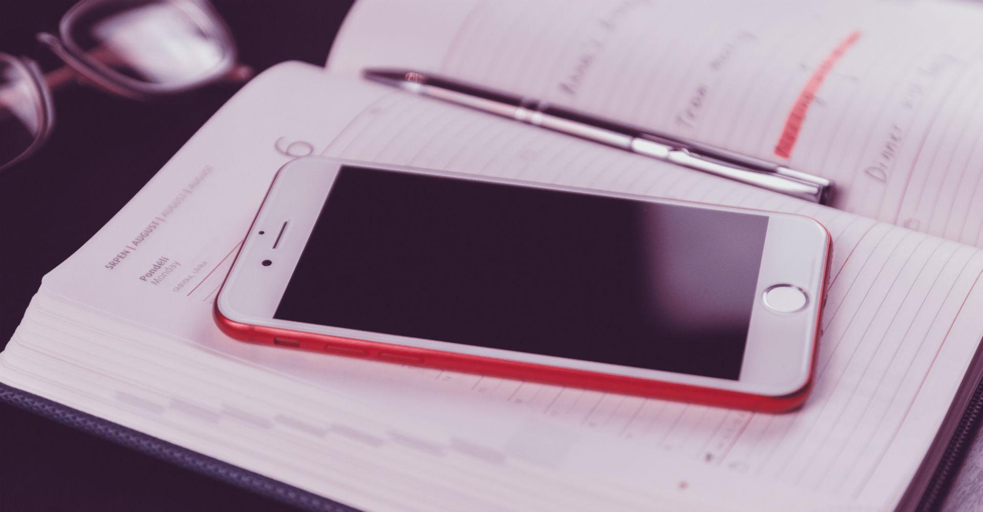 Rotes iPhone 7 liegt auf einem Schreibtisch.