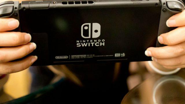 Junge Frau zockt mit der Nintendo Switch.