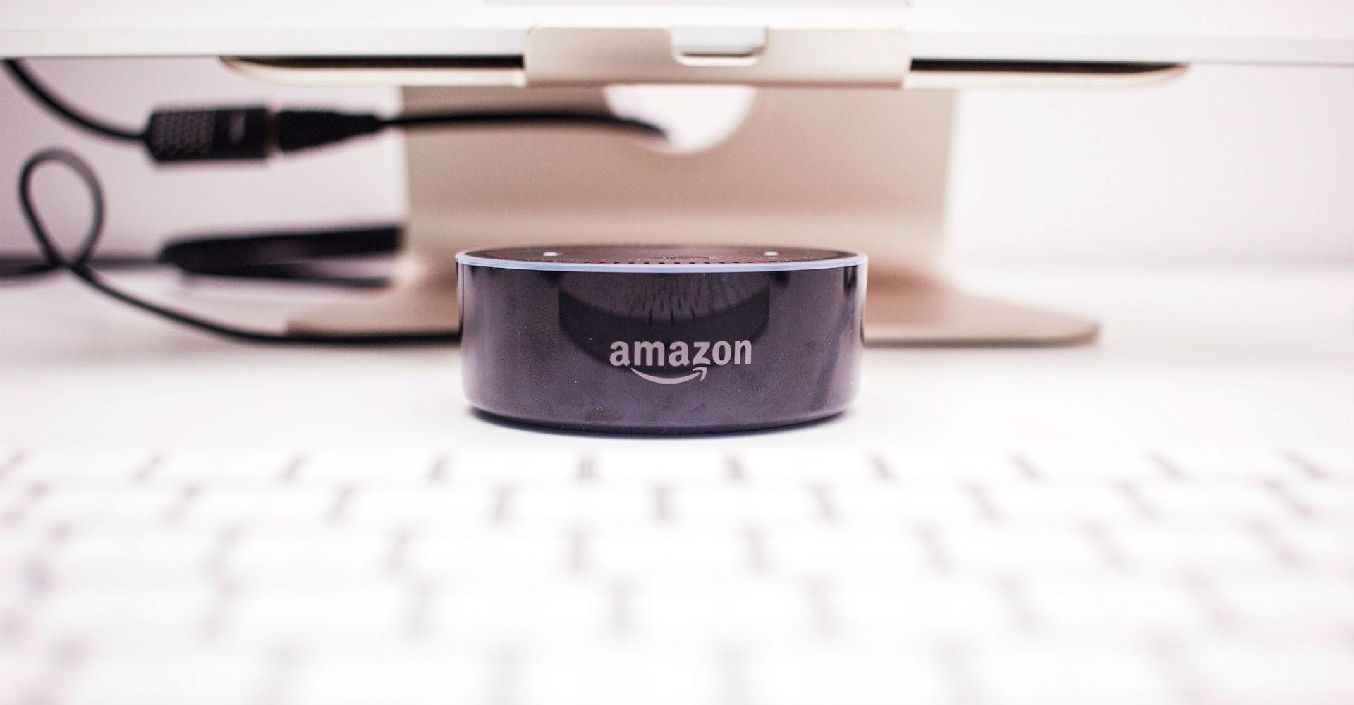 Schwarzer Amazon Echo Dot steht auf dem Schreibtisch vor dem Computer.