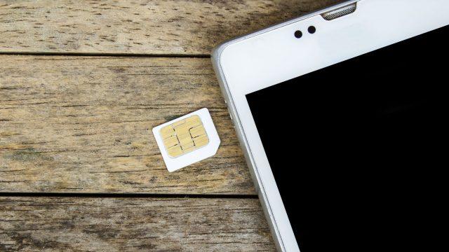 SIM-Karte liegt neben einem weißen Smartphone auf einem Holztisch.