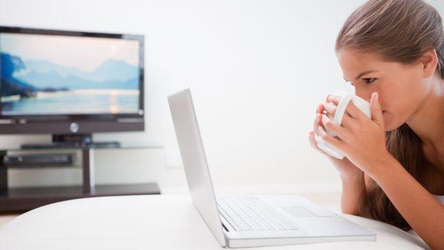 Eine Frau streamt ihren Laptop-Bildschirm auf einen Fernseher