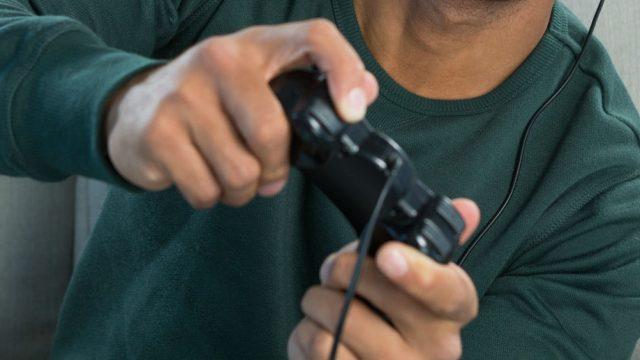 Junger Mann spielt ein Game mit dem PS4-Controller.