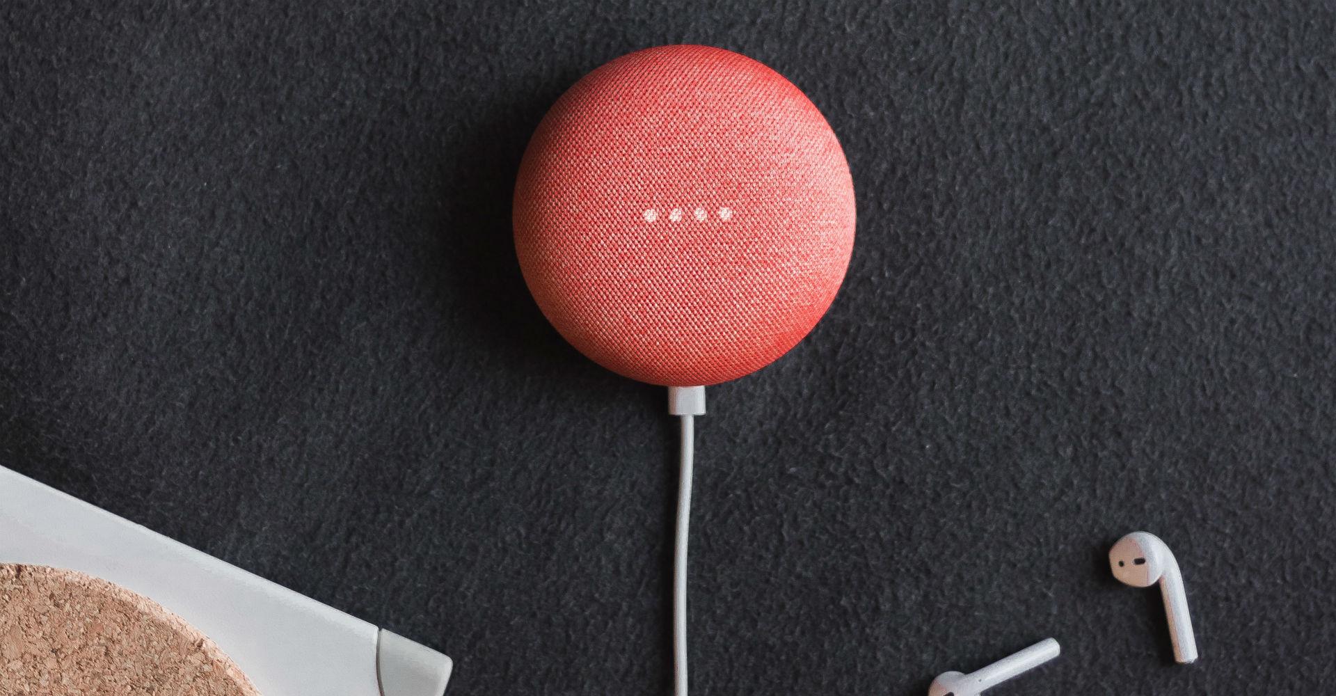 Korallenfarbener Google Home-Mini liegt auf einem schwarzen Schreibtisch.