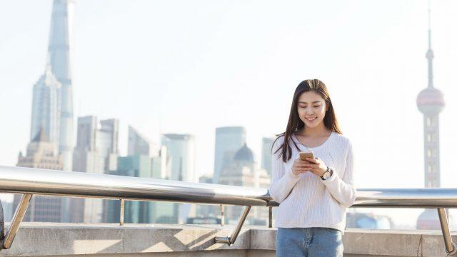 Junge Asiatin ist unterwegs und schaut auf ihr Smartphone
