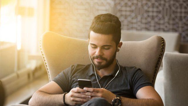Junger Mann betrachtet entspannt Videos auf einem Smartphone
