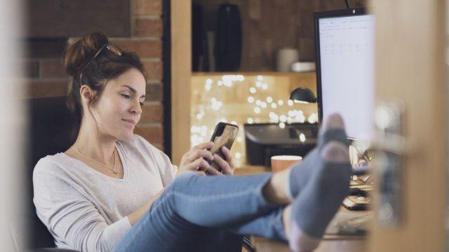 Frau schaut sich Fotos am iPhone an.