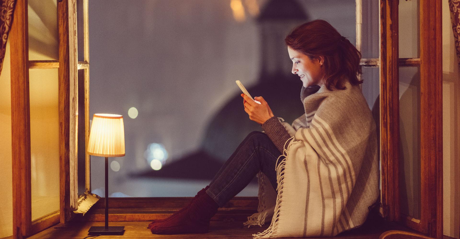 Junge Frau sitzt am Fenster mit ihrem Smartphone und schreibt eine Nachricht.