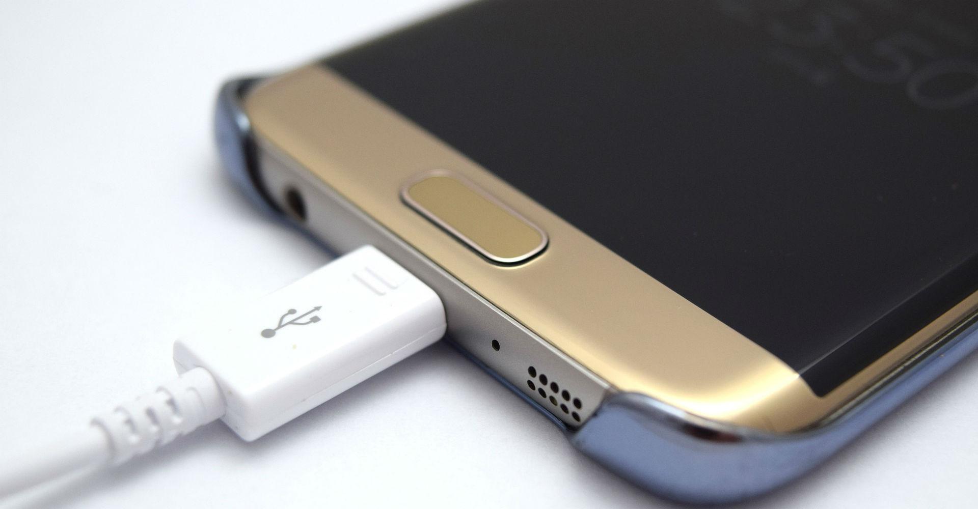 Goldenes Smartphones wird per Kabel aufgeladen.