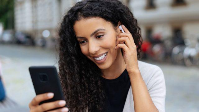 Frau hört mit Bluetooth-Kopfhörern Musik vom Smartphone