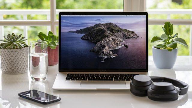MacBook, Smartphone und Kopfhörer auf einem Schreibtisch am Fenster