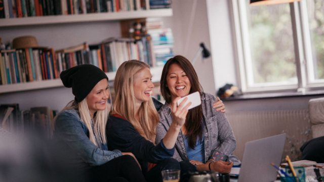 Freundinnen schauen YouTube-Videos am Smartphone.