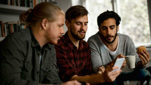 Drei junge Gamer chatten über das Smartphone mit ihrem Freunden.