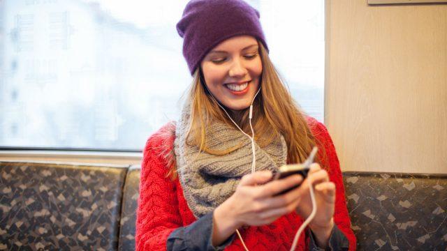 Junge Frau sitzt in der Bahn und nutzt Gehirnjogging-Apps am Smartphone.