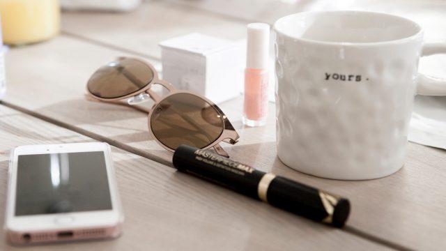 Ein iPhone und eine Kaffeetasse in einer Bürosituation