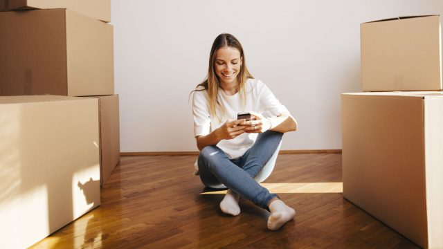 Mädchen sitzt mit neuem Smartphone in der neuen Wohnung.