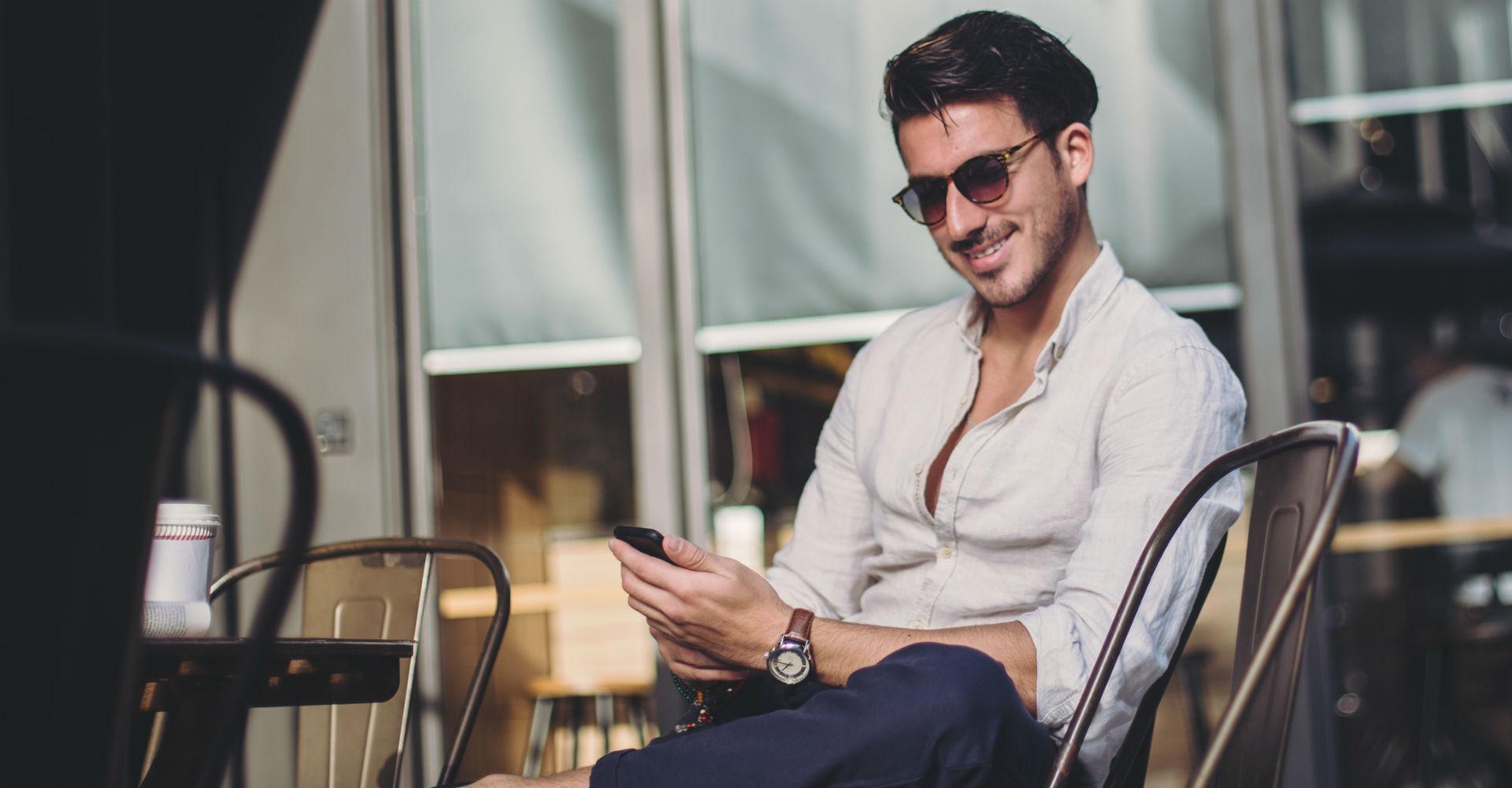 Junger Mann chattet über WhatsApp mit seinen Freunden.