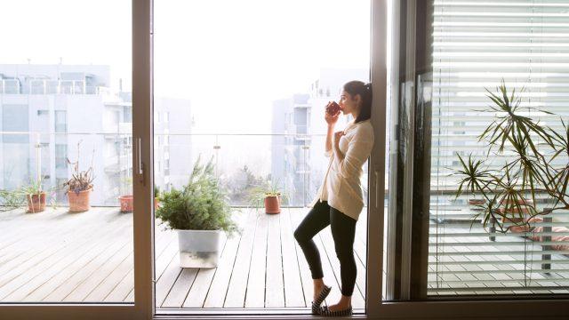 Eine Frau trinkt Kaffee am Balkon