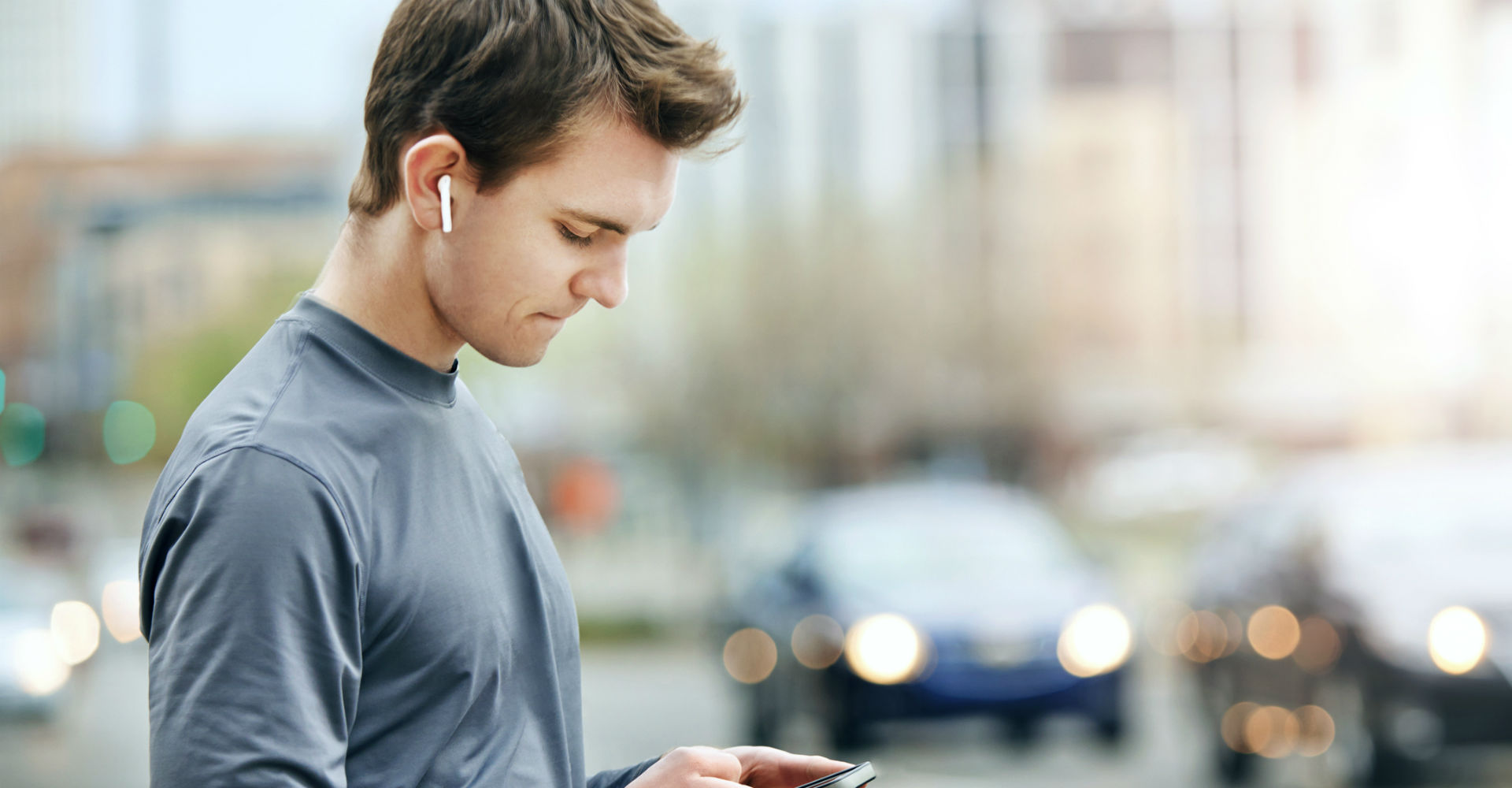 Junger Mann sieht sich auf dem Smartphone den Ladestand seiner AirPods an.