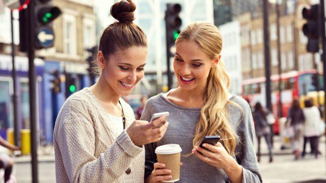 Freundinnen nutzen den Facebook Messenger auf ihren Smartphones.