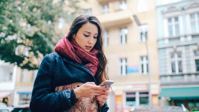 Eine Frau mit Smartphone in der Stadt