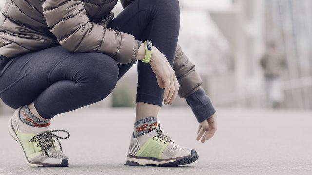 Frau nutzt Fitness-Tracker beim Laufen