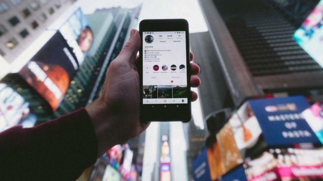 Instagram-Profil auf Smartphone, welches in die Luft gehalten wird.