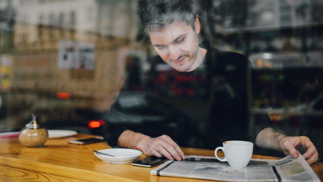 Ein Mann liest die Nachrichten in einem Cafe