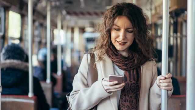 Junge Frau verwendet Instagram auf ihrem Smartphone
