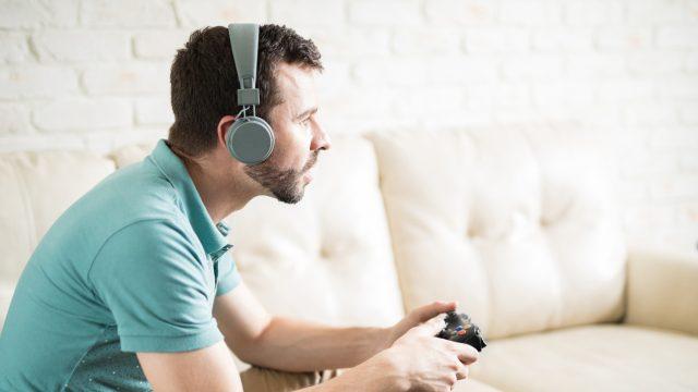 Junger Mann spielt Xbox mit Bluetooth-Kopfhörern