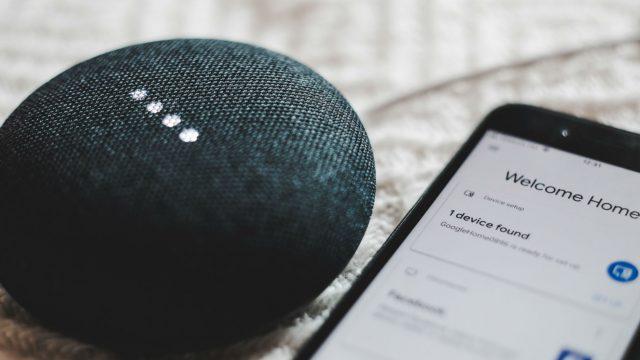 Schwarzer Google Home Mini liegt neben Smartphone.