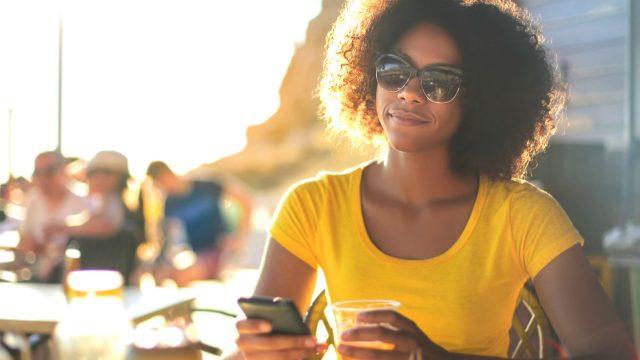 Junge Frau checkt Android Excellence-Gewinner am Smartphone.