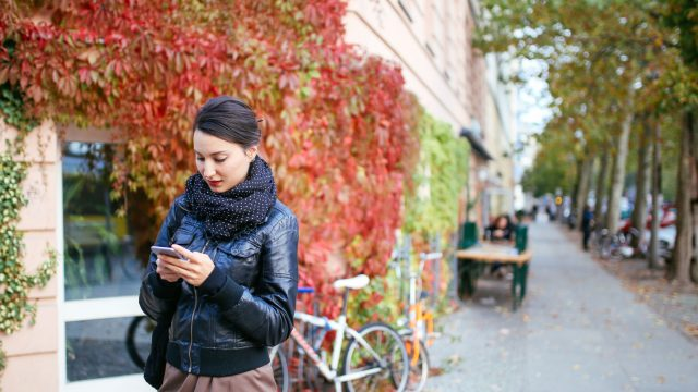 Junge Frau verwendet AirDrop auf ihrem Smartphone.