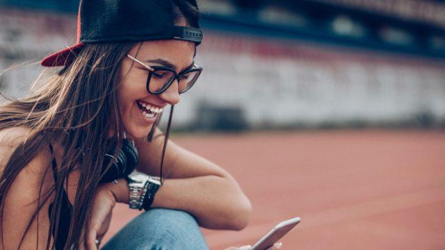 Junge Frau textet ihren Freunden über ihr Smartphone.