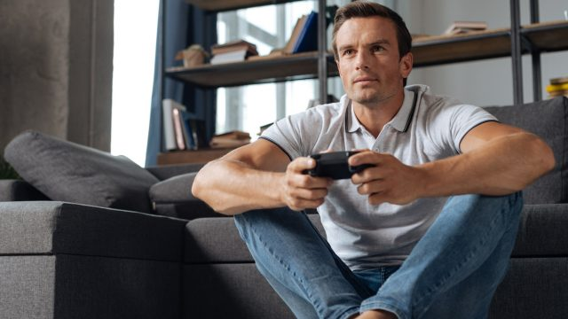 Junger Mann spielt God of War auf Konsole