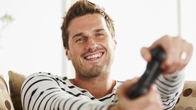 Ein junger Mann spielt PlayStation 4