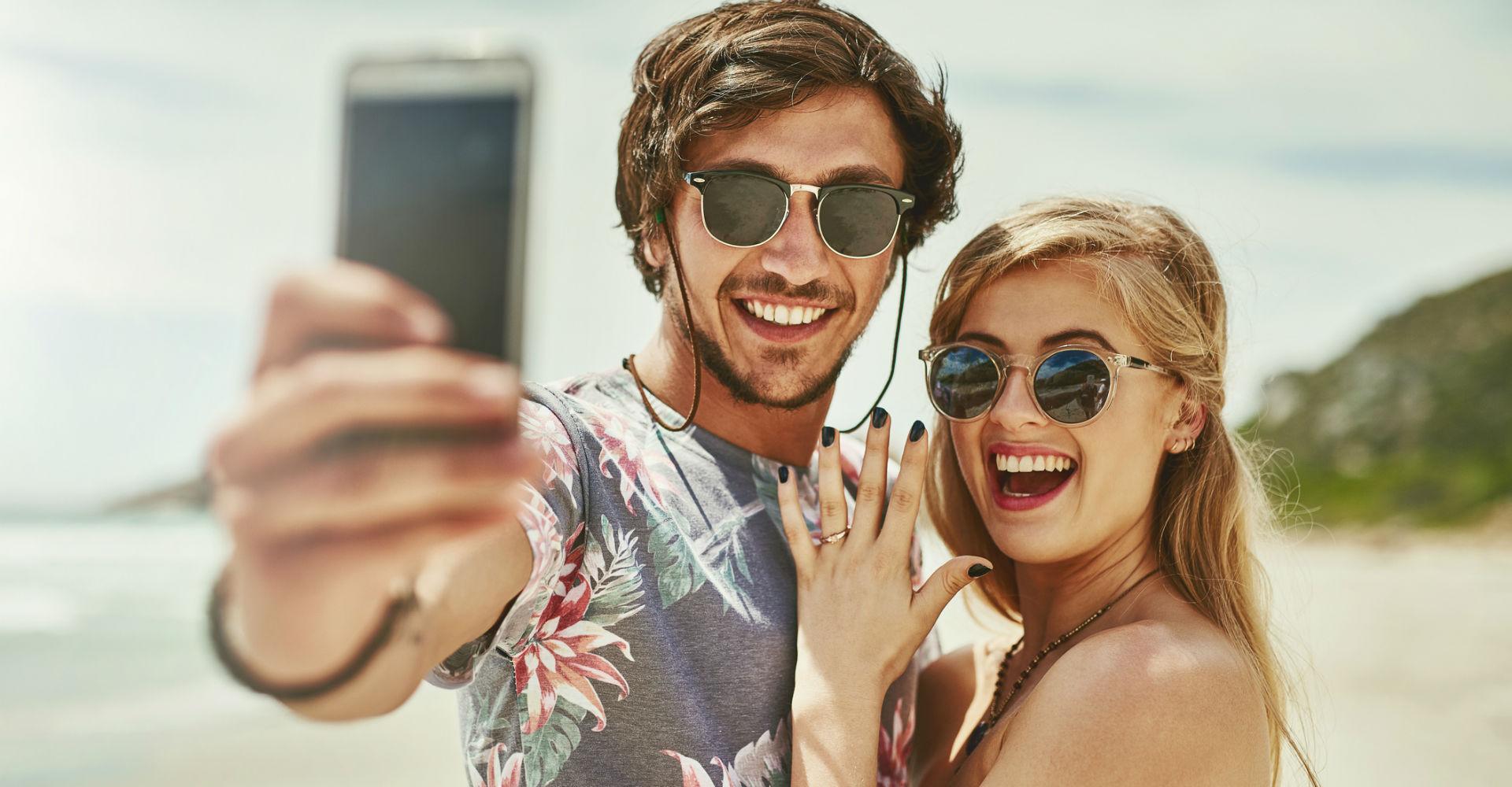 Junges Paar teilt über das Smartphone die freudige Nachricht.