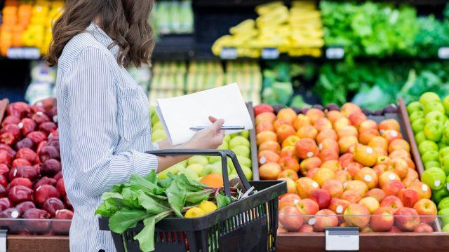 Eine junge Frau geht mit einer Liste einkaufen