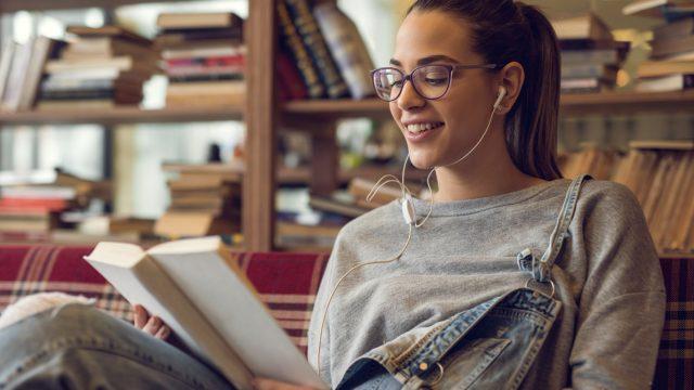 Eine junge Frau hört ein Hörbuch und liest zeitgleich