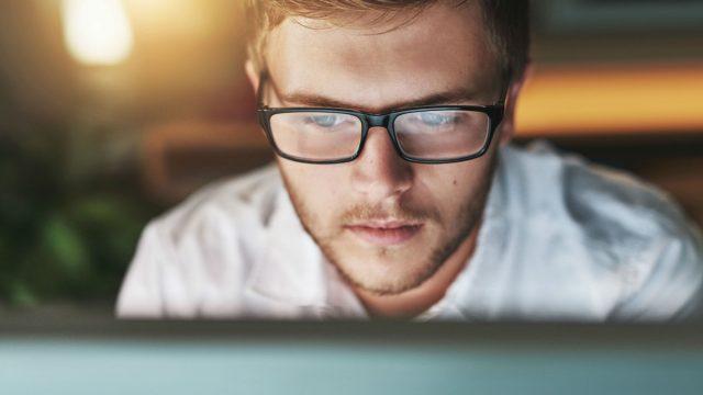 Junger Mann arbeitet am Windows-10-PC.